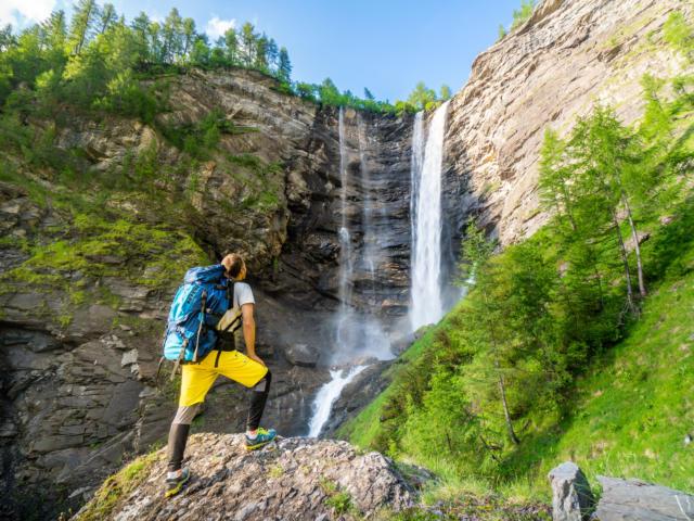 Randonneur face à la cascade de la Pisse au refuge du Tourond